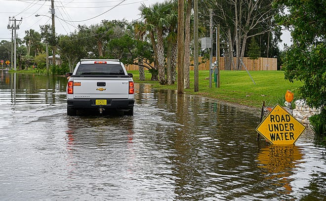 A City of St. Augustine truck drives along a flooded Coquina Avenue in the Davis Shores community in the city at high tide on Monday.