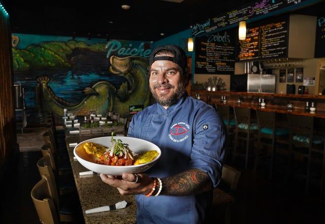 Owner/chef Darwin Santa Maria poses with atun poke inside his restaurant Darwin Peruvian Eatery in Sarasota.