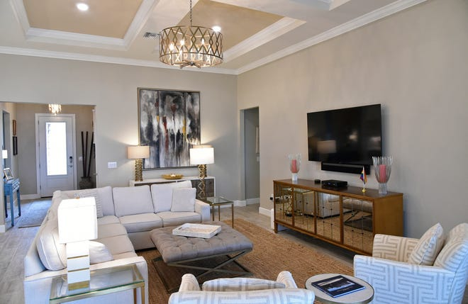 The living room in the new home of Tom Piccoli and David Wagner. They brought the gold-flecked sideboard with them from New Jersey. Everything else was purchased in Sarasota. Rug from Rugs as Art, furniture from Matter Brothers Furniture, chandelier from Bee Ridge Lighting. An upgrade from the basic Pinnacle Model that the homeowners chose is the coffered ceiling. THOMAS BENDER/HERALD-TRIBUNE