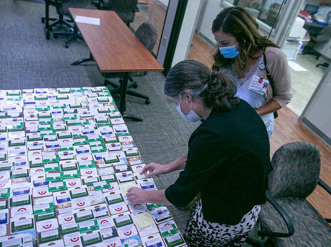 CarolinaEast Foundation director Jill Thompson, in foreground, and communications director Brandy Popp look over gift cards the Foundation is sending as hurricane relief to Louisiana. [Bill Hand / Sun Journal Staff