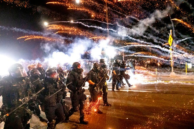 In this Sept. 5 photo, police use chemical irritants and crowd control munitions to disperse protesters during a demonstration in Portland, Ore.