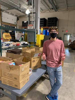 Peter Farquharson takes a break from packing food boxes at the Community Hunger Outreach Warehouse (CHOW). He is one of about 25 volunteers named as CHOW Champions for their extraordinary efforts to help.