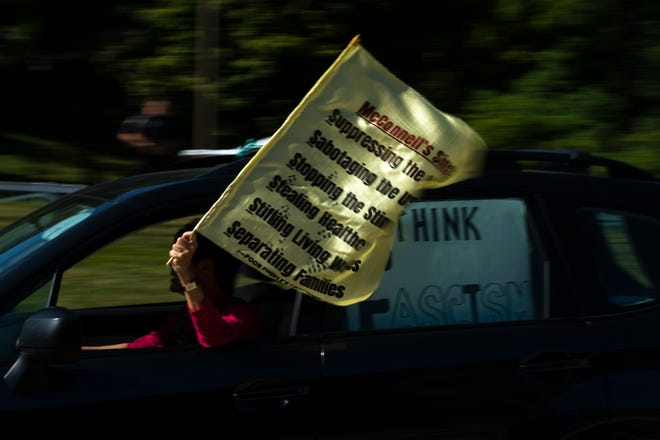 "A protester holds a flag out of her car window during the Poor People's Campaign ""National Call for Moral Revival"" protest of Mitch McConnell's refusal to pass COVID-19 related bills at Sen. Mitch McConnell's office in Fort Wright on Monday, Sept. 21, 2020."