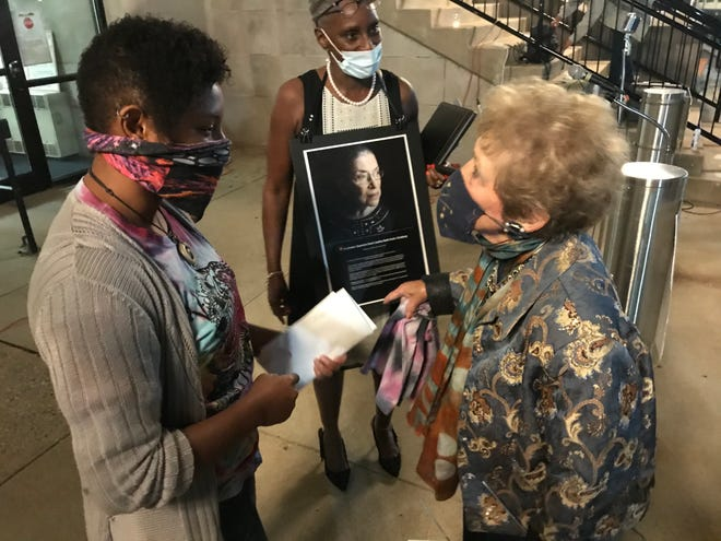 Claire Tchoula, left, listens as state Rep. Sheila Klinker, right, and Sadie Harper-Scott, president of the Greater Lafayette NAACP, thank her for organizing a candlelight vigil Sunday, Sept. 20, 2020, at the Tippecanoe County Courthouse in downtown Lafayette in memory of Supreme Court Justice Ruth Bader Ginsburg.