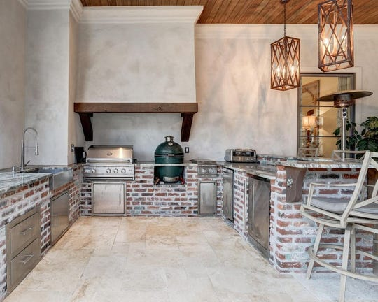 Outside, the full kitchen is next to outside seating with a fireplace. The pool also has a hot tub and fountains.This mansion, on the market for$2.5 million, offers outside kitchen, with a gentlemen's room, in-home theater anda full outside kitchen.