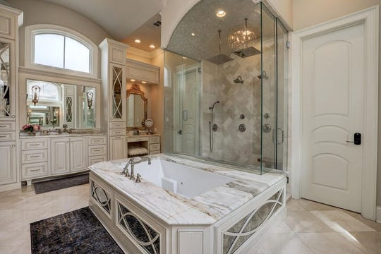 Master bedroom suite features a fireplace, views of the pool, and a stunning master bath with a steam shower and separate closets. This mansion, on the market for$2.5 million, offers outside kitchen, with a gentlemen's room, in-home theater anda full outside kitchen.