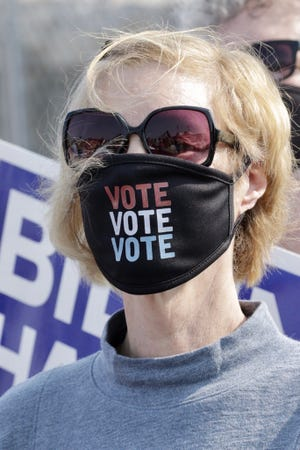 Karen Steingraber, of Newton, Wis., wears a mask endorsing voting as she stands outside the Wisconsin Aluminum Foundry in downtown Manitowoc on Monday, Sept. 21. Democratic presidential candidate and former vice president Joe Biden was making an appearance at the foundry.