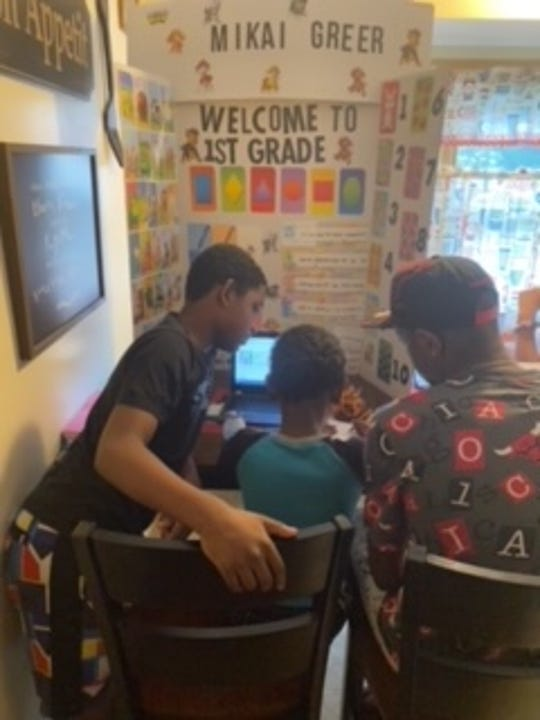 Mikai Greer does virtual school with help from his brother, Kobe Matthews and his father, Sergio Greer.