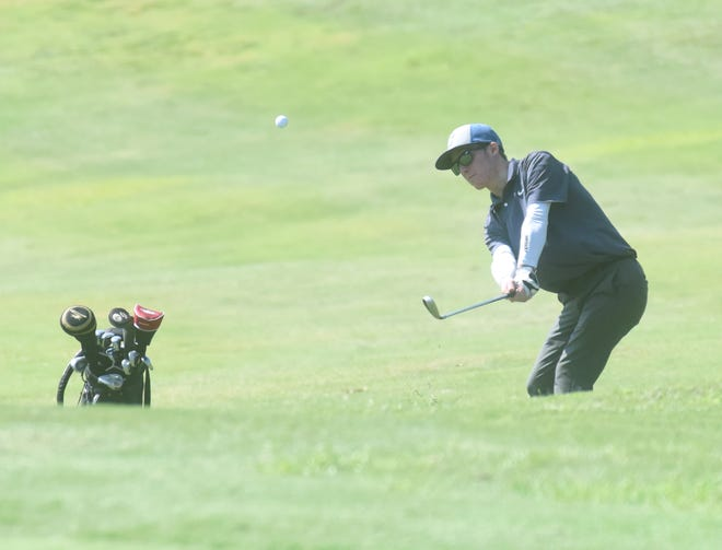 Cotter's Christian Cloyd pitches onto the green on Monday at the 2A-1 District golf tournament.