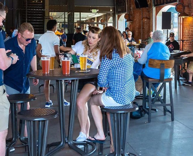Guests can reserve tables in Riverwalk Stadium's Club Car Bar to watch college football while enjoying food and drinks from the Biscuits.