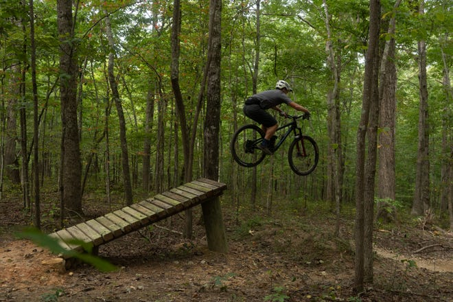 A rider takes off from a jump in the newly opened Wilkins Branch Mountain Bike Park in southern Williamson County on Sept. 20, 2020.
