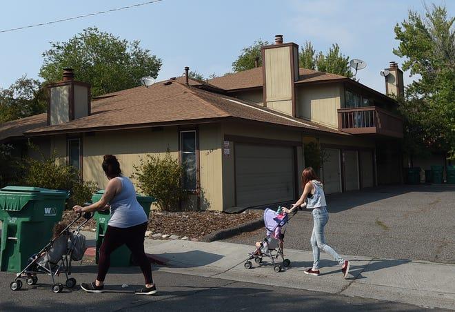 Women pushing strollers walk past 1235 Berrum Lane in southwest Reno where a boy was found dead Sept. 18, 2020.
