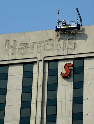 """The """"S"""" from the Harrah's sign on the south side of west tower of the former Harrah's Reno Hotel and Casino is lowered while being removed on Monday Sept. 21, 2020."""