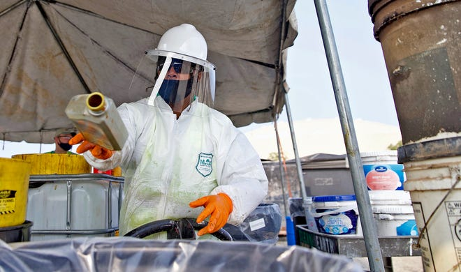 A worker processes materials at a household hazardous waste disposal event held by Keep San Angelo Beautiful at the Foster Coliseum on Saturday, Sept. 19, 2020.