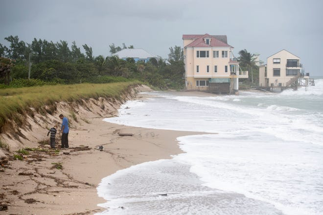 "Brenden McIntosh, 8, and his father Carl McIntosh, of West Palm Beach, explore the coastline Monday, Sept. 21, 2020, at Bathtub Reef Beach on Hutchison Island in Martin County. Near tropical storm-force winds with a weekend cold front and high tides from Hurricane Teddy damaged shoreline and created dangerous sea conditions across the Treasure Coast. ""The birds are even scared of the water,"" said Brenden McIntosh."