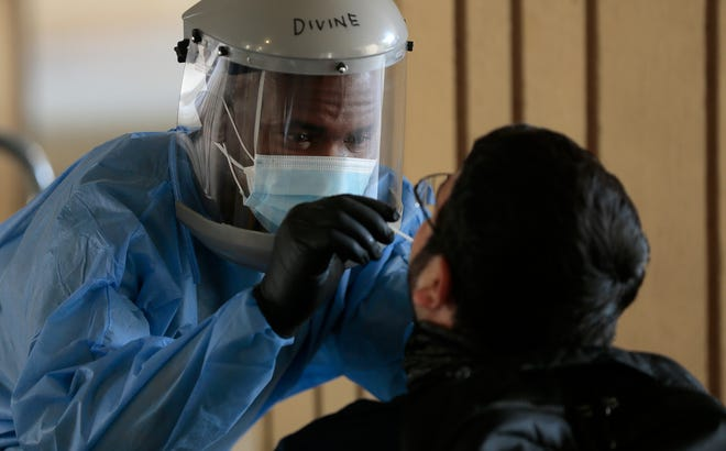 Divine Ayong collects a coronavirus sample for testing Monday, Sept. 21, 2020, at UTEP's Fox Fine Arts Building.