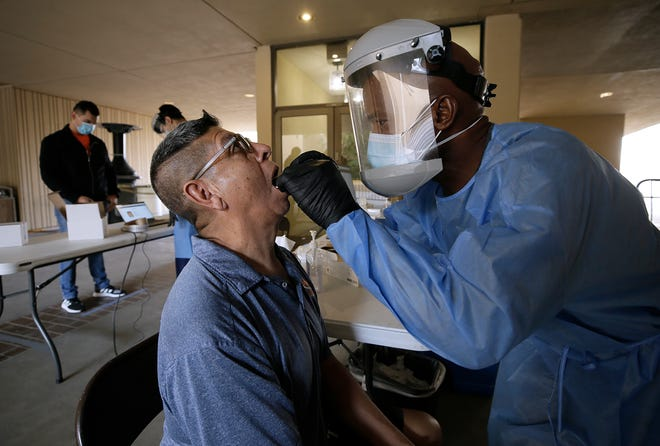 Divine Ayong collects a sample from UTEP staff member David A. Duran for coronavirus testing Monday, Sept. 21, 2020, at UTEP's Fox Fine Arts Center.