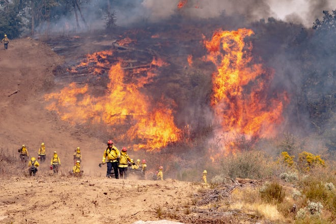 Local CALFIRE firefighters from the Tulare unit fire off fuels Sunday, September 20, 2020 along a dozer break, left, for the SQF Complex Fire along Bear Creek Road. The effort was toprevent the fire from approachingareas near Springville.
