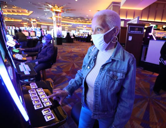 Evelyn Garcia of The Bronx plays a slot machine on the first day of the reopening of the Empire City Casino in Yonkers Sept. 21, 2020.