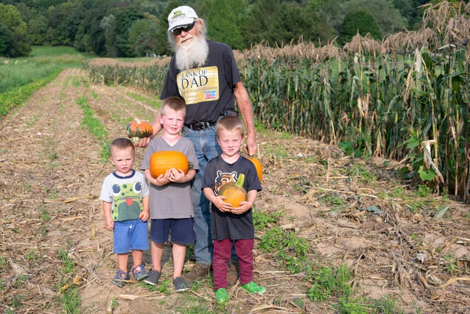 Terry Paul sends his grandsons, Terrence, 5, Colton, 4, and Oliver, 2, home with pumpkins they picked from the patch.