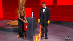 In this video grab captured on Sept. 20, 2020, courtesy of the Academy of Television Arts & Sciences and ABC Entertainment, Jennifer Aniston, left, and Jimmy Kimmel sanitize the winner's envelope while presenting the award for outstanding lead actress in a comedy series during the 72nd Emmy Awards broadcast.