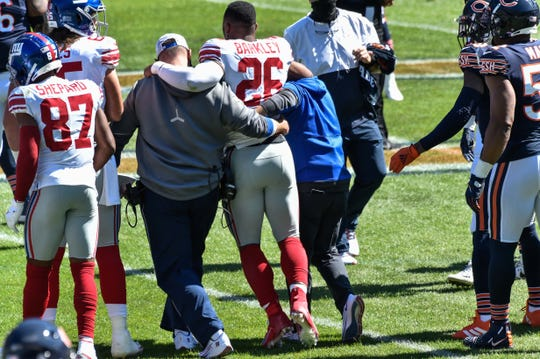 Saquon Barkley is helped off the field after suffering an injury during the second quarter against the Chicago Bears.