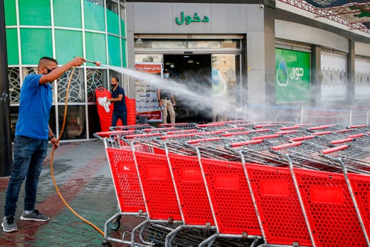 A Palestinian worker disinfects supermarket carts as part of COVID-19 coronavirus pandemic precautions outside a supermarket in Gaza City on Sept. 21, 2020.