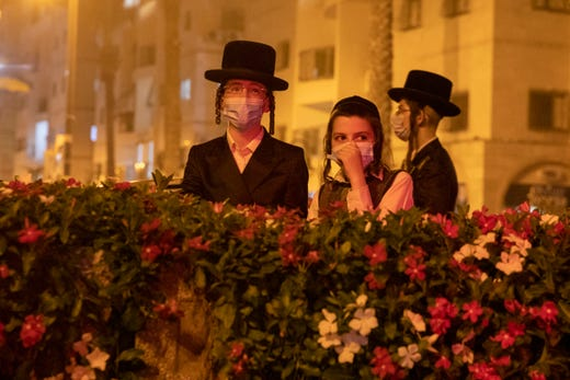 Ultra-Orthodox Jews protest against the restrictions on gatherings for public prayers despite a new nationwide lockdown order aimed at curbing a raging coronavirus outbreak in Bnei Brak, Israel, Sept. 20, 2020. In the ultra-Orthodox town of Bnei Brak near Israel's commercial hub of Tel Aviv, over 100 activists took to the streets and burned garbage to protest restrictions on gatherings for public prayers.