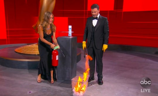"""Jennifer Aniston and Jimmy Kimmel """"sanitize"""" the winner's envelope with a literal dumpster fire while presenting the award for outstanding lead actress in a comedy series during the mostly remote 72nd Emmy Awards broadcast."""