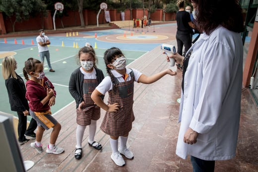 First grade students wearing protective face masks line up to have their temperature taken before entering the school building at the Florya Ugur College on Sept. 21, 2020 in Istanbul, Turkey. For the first time since schools closed on March 16, due to the coronavirus outbreak, kindergarten and first grade students were allowed to return for in-person classes at schools across Turkey. The one day a week classes are voluntary and restarted amid strict coronavirus precautions. As coronavirus cases continue to spike around the globe many families continue to opt for online classes.