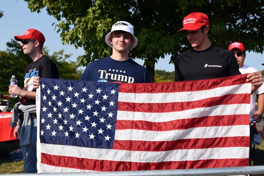 Trump supporters James Chick, 19, left, and Tony Zona, 18, both from Irwin, Pa., hold up an American flag as they wait in line at Atlantic Aviation at the Greater Pittsburgh International Airport Tuesday for a