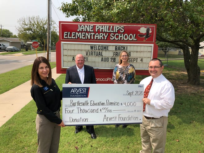 Arvest local bank president Kim Adams presents a check for $4,000 from the Arvest Foundation to Jane Phillips Elementary School principal Kevin Brown, Bartlesville Education Promise Chairman Martin Garber and Vice Chair Vanessa Drummond.
