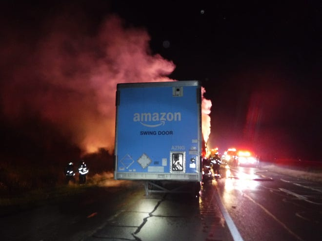 Firefighters from Barnesville and Old Washington fire departments work to extinguish  a fire in the trailer of an Amazon Prime truck on I-70 W near Barnesville on Friday night.