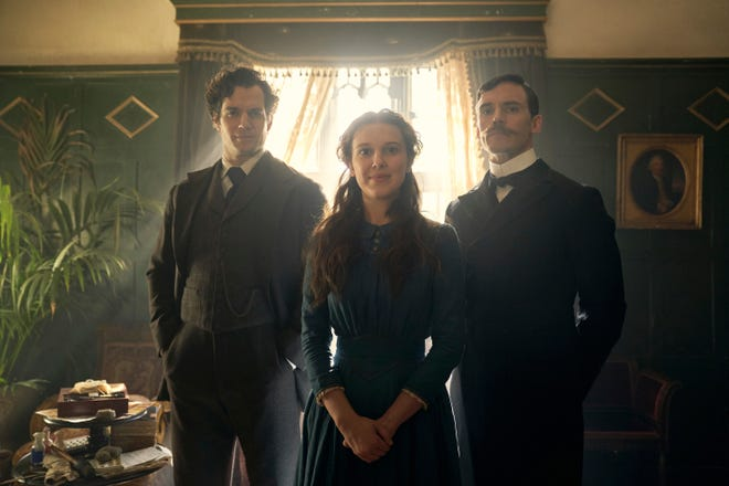 "This image released by Netflix shows Henry Cavill, from left, Millie Bobby Brown and Sam Claflin in a scene from ""Enola Holmes."""