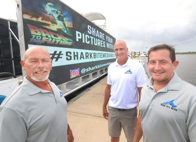 "The Shark Bite Media team, from left, captain Buddy Simmons, director of sales and marketing Tim Pulnik, and owner Rob Guariallo, with the 60-foot barge, outfitted with two giant 40-foot LED billboards and over 2.5 million LED lights, Tuesday, Sept. 22, 2020 at the Sea Love Marina in Ponce Inlet. The craft is typically used for advertising but will play ""Back to the Future"" for a movie night on Disappearing Island on Sept. 26."