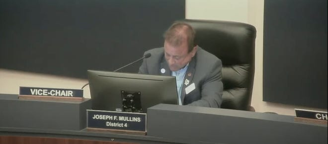 Commissioner Joseph Mullins reads aloud his emailed apology to commissioners Monday night.