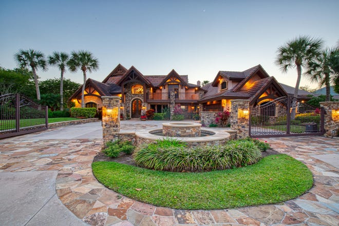 Impressive front gates open to this Strasser-owned-and-built waterfront estate on sought-after John Anderson Drive.