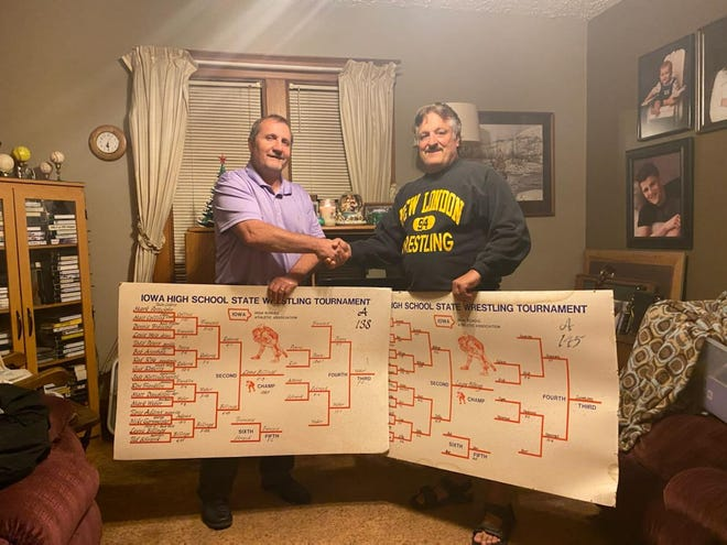 Layne Billings (left) receives his state wrestling championship brackets from New London High School head wresting coach Mark Chiri.
