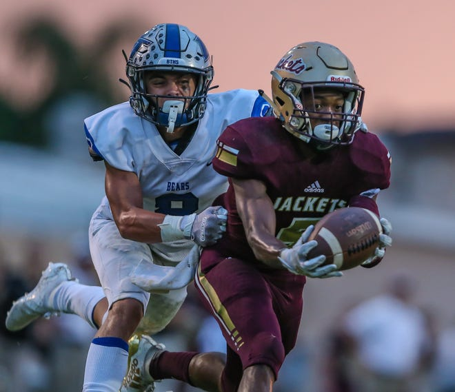 St. Augustine wide receiver Dequan Stanley (5) catches a pass defended by Bartram Trail defensive back Evan Eilers (8) during the first half of a high school football at St. Augustine High School in St. Augustine, Fla., Friday, Sept. 20, 2019.  [Gary Lloyd McCullough/ Correspondent]