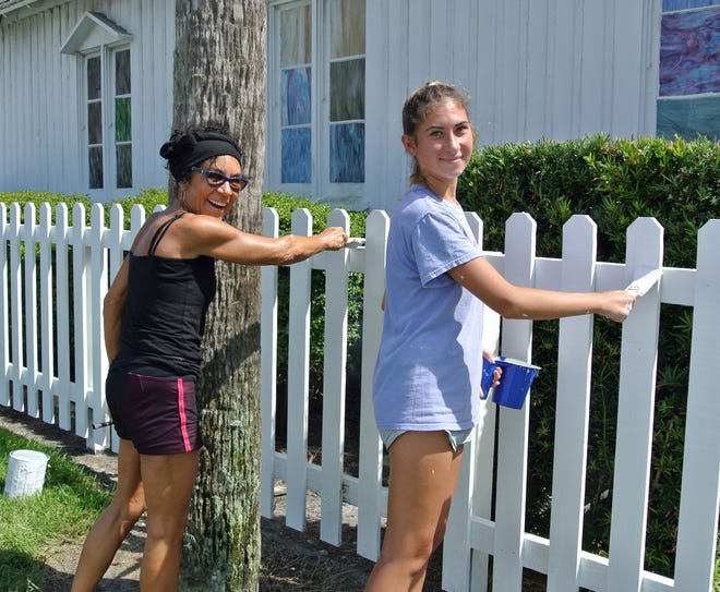 Sherry Black (left) and Olivia Derechin had fun painting the Beaches Museum and History Park picket fence on Sept. 4-5.