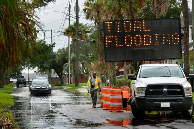 Mike Calloway of Bob's Barricades sets up a warning sign on LaSalle Street  in San Marco this week as  recent rains, high tides and nor'easter conditions caused the St. Johns River to back up into local neighborhoods.