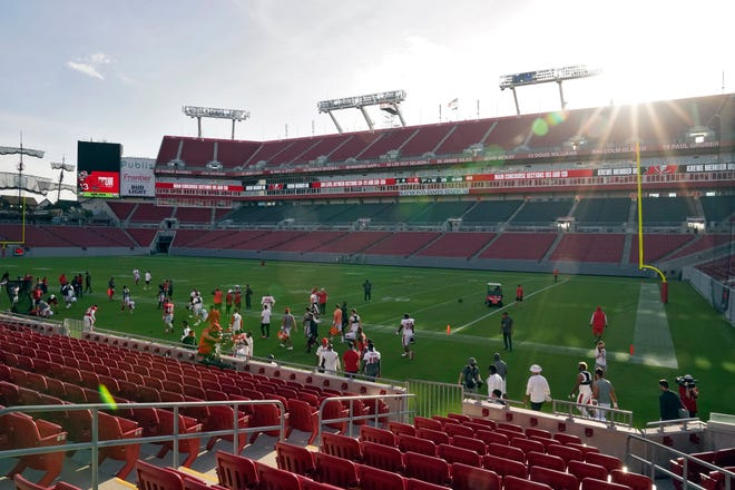 The sun rises over Raymond James Stadium as the Tampa Bay Buccaneers take the field for a training camp practice in August.