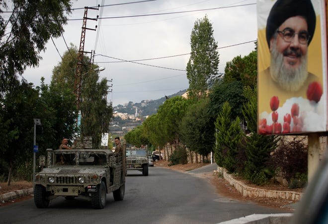 Lebanese army vehicles pass next to a portrait of Hezbollah leader Sayyed Hassan Nasrallah on Tuesday, as they patrol on a road that leads to the site of an explosion that rocked a Hezbollah stronghold, in the southern village of Ain Qana, Lebanon. The powerful explosion sent thick grey smoke billowing over the village, but the cause was not clear.
