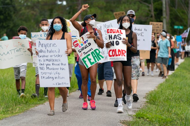 Brandi Kennedy, left, Kristy Ferrer, center and Madison Hollingshed, right, lead demonstrators marching against racism west of Jupiter in June. [GREG LOVETT/palmbeachpost.com]