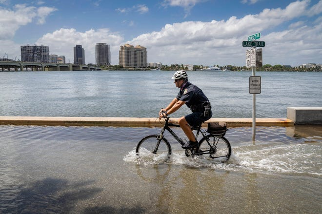 Police officer Anthony DeJesse rides through the water on Lake Trail during high tide Tuesday in Palm Beach. [GREG LOVETT / palmbeachpost.com]