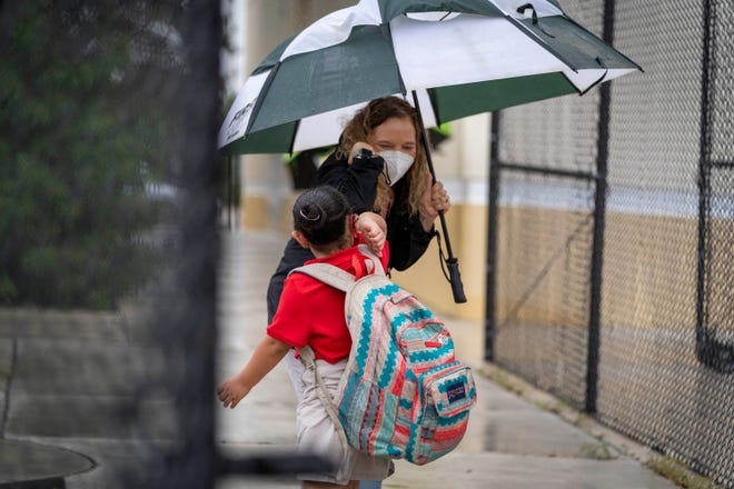 School counselor Luz Williams does an elbow bump as she greets a student arriving on the first day of school at North Grade Elementary School in Lake Worth Beach, Florida on Monday, Sept. 21, 2020.