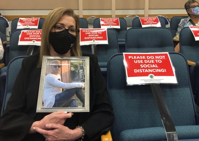 Michelle held a framed photo of her son Brice, who died of an overdose at age 23 on March 12.   Michelle Makris of Boca Raton holds a framed photo of her son Brice, who was 23 when he died of a opioid overdose on March 12. Makris attended a Palm Beach County Commission meeting to support the county's efforts in the opioid crisis, which has been been affected by the COVID-19 pandemic. Although she said Brice's death was probably not related to the pandemic, she said his was one of the last funerals held before funerals were affected by the coronavirus closures.