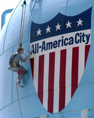 A worker paints the water tower in Delray Beach. (PALM BEACH POST FILE PHOTO)