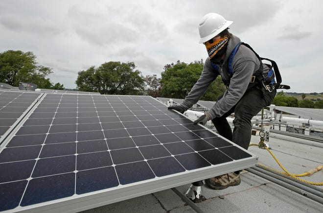 Gen Nashimoto, of Luminalt, installs solar panels in Hayward on April 29. Elk Grove Assemblyman Jim Cooper says it is time meaningful equity issues such as the cost of living, electricity reliability and cost be made a priority in California's energy policymaking.