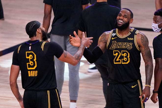 Los Angeles Lakers Anthony Davis and LeBron James (23) celebrate Sunday's 105-103 win over the Denver Nuggets in Game 2 of the Western Conference finals in Lake Buena Vista, Fla. Game 3 is Tuesday night.